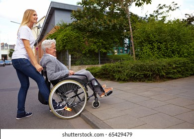 Young woman helping elderly woman in wheelchair over a curbstone