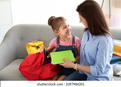 Young woman helping her little child get ready for school at home