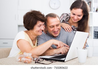 Young woman helping her senior parents to learn how to use laptop at home