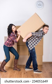Young woman helps her husband to lift a box.