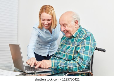 Young woman helps senior at laptop computer and explains internet and social media