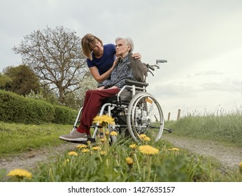Young woman helps senior woman in wheelchair