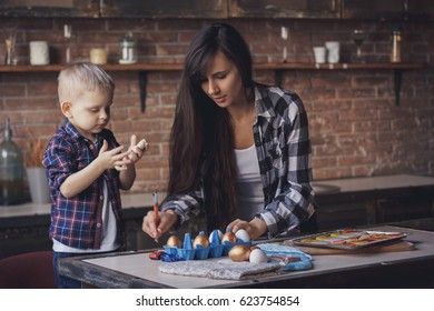 Young woman with her 2 years old son painting Easter eggs in the kitchen