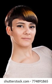 Young woman in her 20s with short hairstyle smiling and looking at the camera. Studio portrait, black background