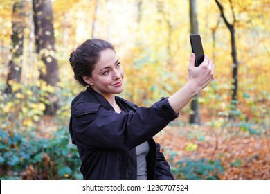 young woman in her 20s taking selfie self portrait with her smartphone mobile phone during autumn walk in forest