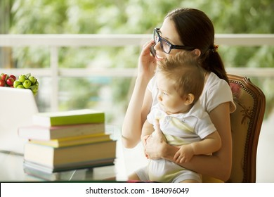 young woman with her baby talking on phone at home