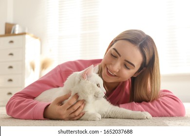 Young woman with her beautiful white cat at home. Fluffy pet