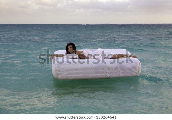 young woman in her bed adrift in the ocean