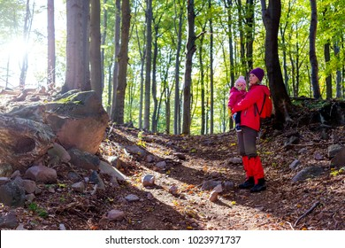 Young woman and her child enjoy nature in the woods.