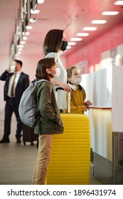 Young woman with her children in protective masks check-in before flight at the airport