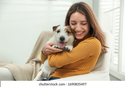Young woman with her cute Jack Russell Terrier at home. Lovely pet