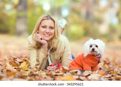 Young woman and her cute little Maltese dog lying among autumn leaves in a park