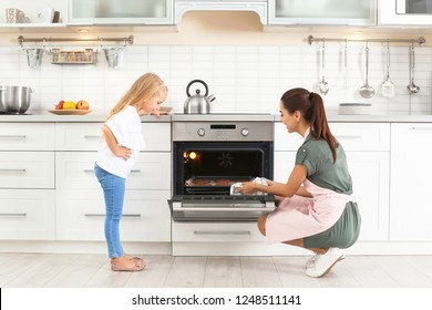 Young woman and her daughter baking cookies in oven at home