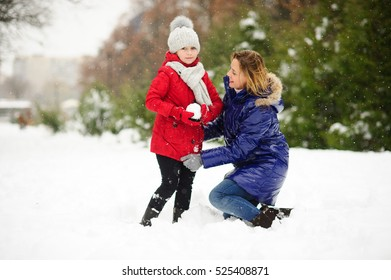 Young woman and her daughter builds snowman. Woman and girl are dressed in bright and warm jackets. It is snowing. Mom lovingly corrects daughters jacket. All earth is covered with fluffy snow.