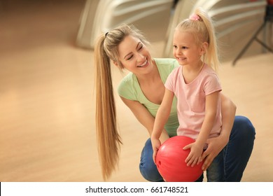 Young woman and her daughter having fun at bowling club