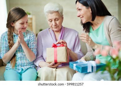 Young woman and her daughter looking at senior female unpacking gift