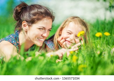 Young woman and her daughter lying on green summer grass with blooming yellow dandellions