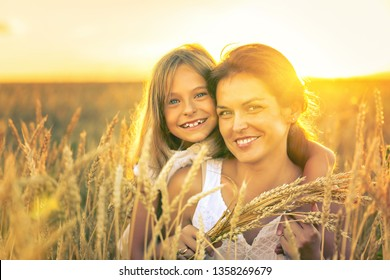 Young woman and her daughter on golden wheat field at sunny summer evening.