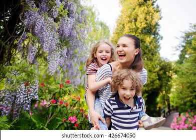 Young woman with her daughter and son on a background of a blossoming garden. They are all very fun. Mom carries a girl on his shoulders. Seven surround flowering plants. Sunny summer day.