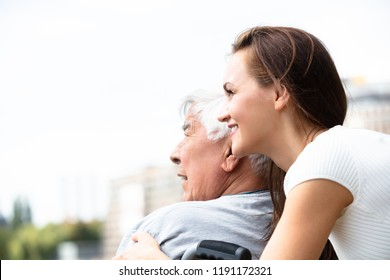 Young Woman With Her Disabled Father Near Railing At Outdoors