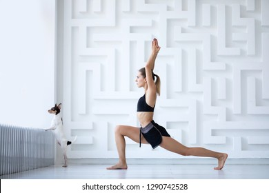 Young woman and her dog doing yoga at home together. Having home yoga class.