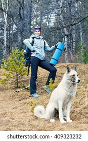 Young woman and her dog hiker in the woods. Keeps hands carpet of blue color on a background of pine forest spring.
