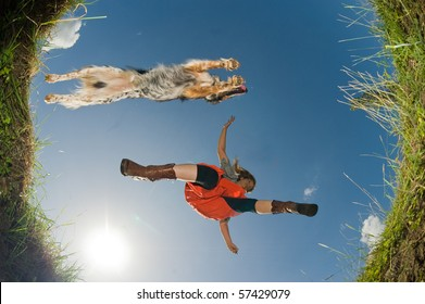 Young woman and her dog jumping over a creek, shot from below.