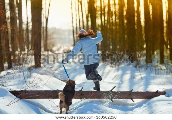 Молодая женщина с ее собакой прыгает через журнал в снежной зимой