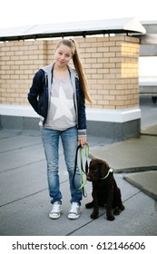 Young woman with her dog labrador retriever standing against brick wall