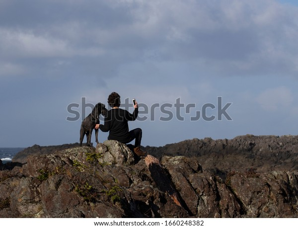 Young woman and her dog sitting on rocks taking a selfie with her phone.
