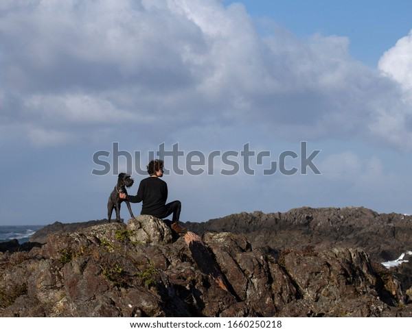 Young woman and her dog sitting on rocks looking off in the distance.
