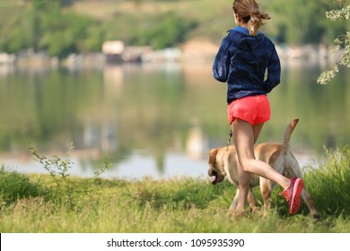 Young woman and her dog spending time together outdoors. Pet care
