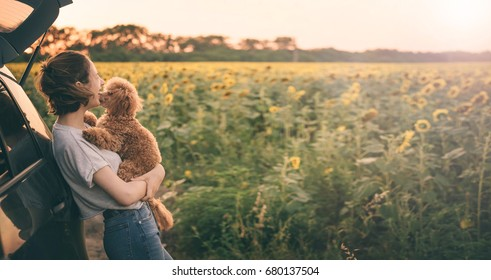 Young woman with her dog standing near the car  . Conceptual freedom, travel and holidays image with copy space.