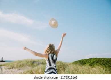 Young woman with her hat flying in the sky
