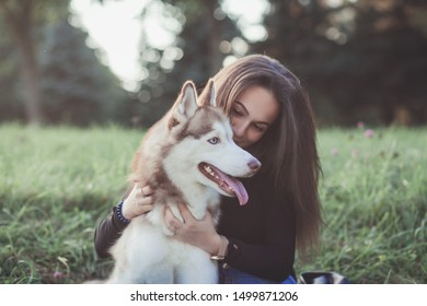 Young woman and her husky dog lying in the grass. Vintage style