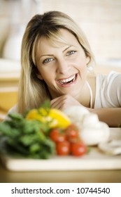 young woman in her kitchen, behind fresh ingredients