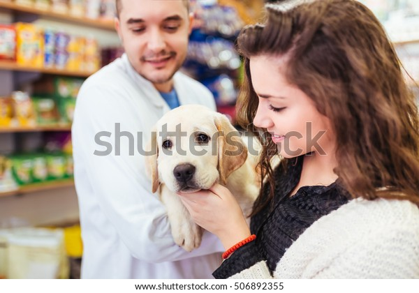 Young woman with her labrador retriever puppy at veterinary.