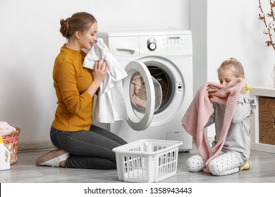 Young woman and her little daughter doing laundry at home