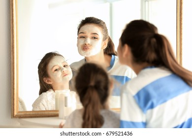 Young woman and her little daughter with facial masks at home