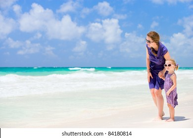 Young woman and her little daughter walking along beach