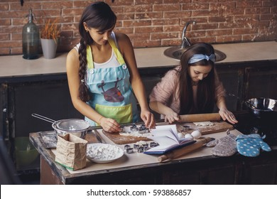 Young woman with her little sister cooking holiday pie in the kitchen