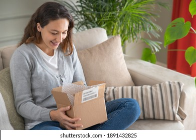 Young woman in her living room looks happy as she unpacks a small cardboard box containing something exciting