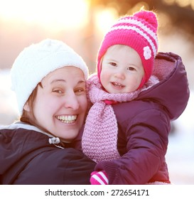 Young woman with her lovely child outdoor in winter