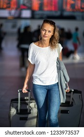 Young woman with her luggage at an international airport, before going through the check-in and the security check before her flight