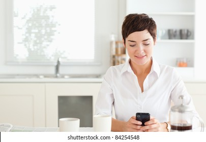 A young woman with her mobile phone and a cup of coffee in the kitchen