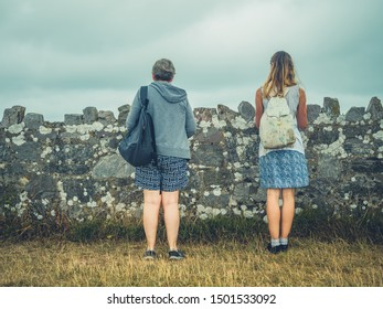A young woman and her mother are standing by a wall in the fog on the coast