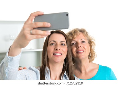 young woman and her mother taking a selfie together in the kitchen