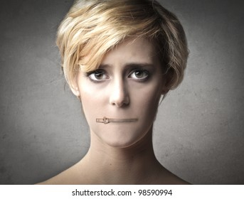 Young woman with her mouth closed by a zipper