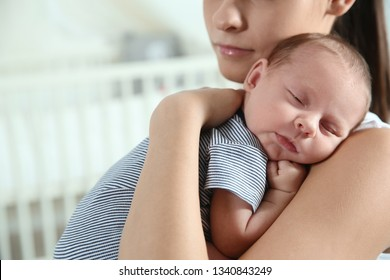 Young woman with her newborn baby at home, closeup