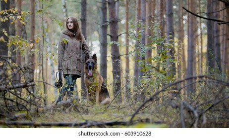 Young woman and her pet - german shepherd - walking on a autumn forest
